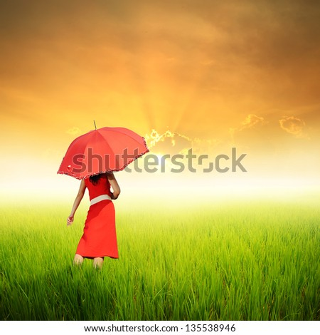 Red Woman holding umbrella in green rice fields in sunset
