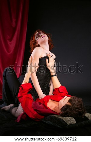 red woman in mask on man - love scene - stock photo