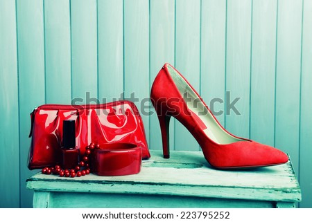 Red women shoes and beautician on wooden background - stock photo