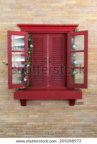 Red wood window in old brick wall. - stock photo