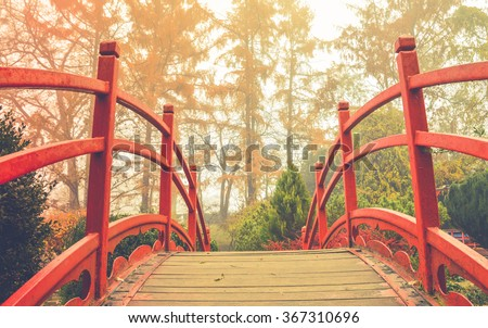 red wooden bridge in soft light wooden bridge with the red handrails in a japanese garden