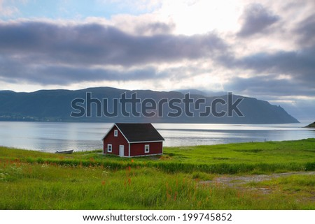 Red wooden cabin on the shore in Nordic landscape - stock photo
