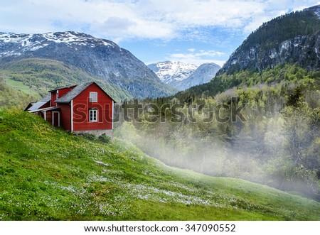 Red wooden cottage in the foggy valley. Green grass, white flowers. Stone snowy mountains. Stalheim, Norway. Mist. - stock photo