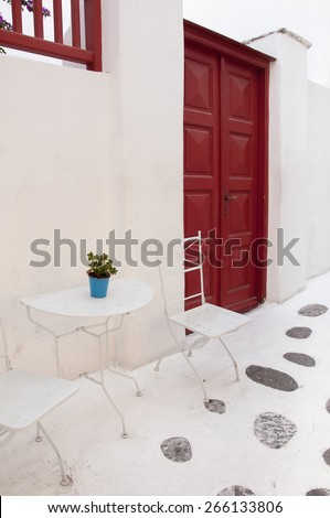 Red wooden door and cafe tables in the narrow streets of Mykonos. - stock photo