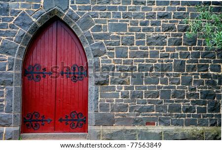 red wooden door in bluestone church - stock photo