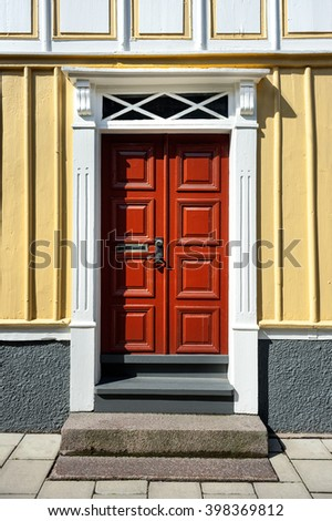 Red wooden door of a yellow house with door handle and mailbox slot