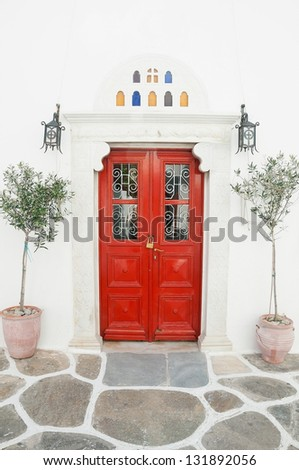 Red wooden door surrounded by marble and olive trees in pots. Mykonos. Greece. - stock photo