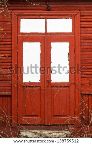 Red wooden door with white windows.
