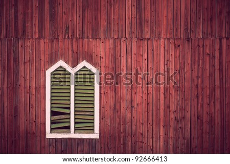 Red wooden rustic wall with window and broken shutters - stock photo