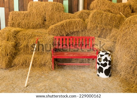 red wooden seat in dry straw  background at farmhouse - stock photo