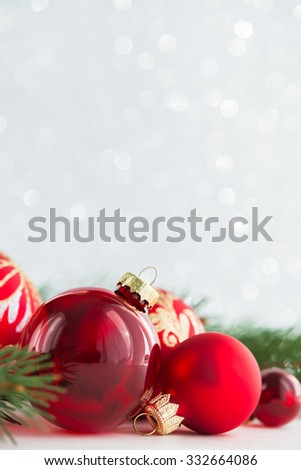 Red xmas ornaments and xmas tree on glitter holiday background. Merry christmas card. Winter holidays. Xmas theme. Space for text. Happy New Year. - stock photo