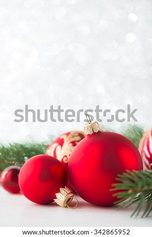 Red xmas ornaments and xmas tree on glitter holiday background. Merry christmas card. Winter holidays. Xmas theme. Happy New Year. Space for text. - stock photo