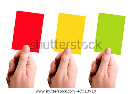Red, yellow and green cards held by hand over a white background - stock photo