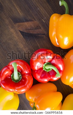 red ,yellow,orange papper on wooden table ,selective focus on green part - stock photo