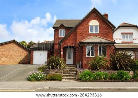 Redbrick english house with garage - stock photo