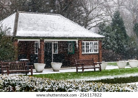 Redbrick House in a Park. Christmas Scenery and Fresh Snow. Cloudy Day. Battersea Park, London - stock photo