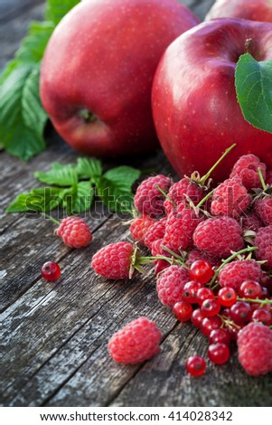 Redcurrant, rasberry and red apples on old wooden table, mix of red color vitamins concept - stock photo