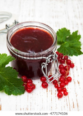 Redcurrants jam with fresh berries on a wooden background