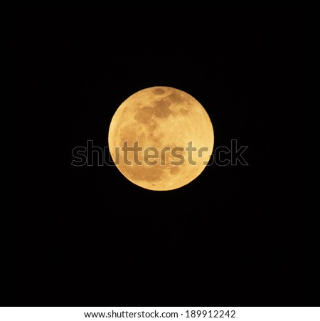 Reddish full moon at low altitude in the sky. Reddish since light other then red is easily scattered by particles in the atmosphere, and red light becomes the most prominent source of color. - stock photo