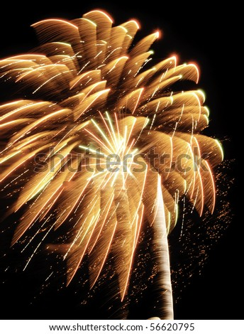 Reddish-orange burst of fireworks with motion blur, one small white-hot burst, feathery rocket trail, streaks, and glitter - stock photo