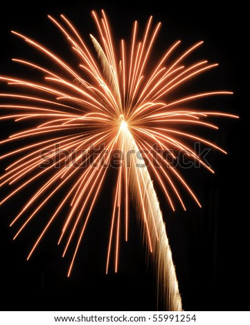 Reddish-yellow burst of fireworks with slightly arched rocket trail - stock photo
