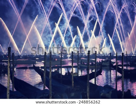Redentore holiday, Redeemer festival of fireworks, people in gondolas swimming along canal and enjoying majestic salute in the sky, Venice, Italy, - stock photo