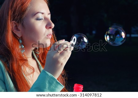 Redhair women is blowing soap bubbles on dark background. Young happy redhead girl having fun with childrens play. Side view, toned image, a lot of space for text - stock photo