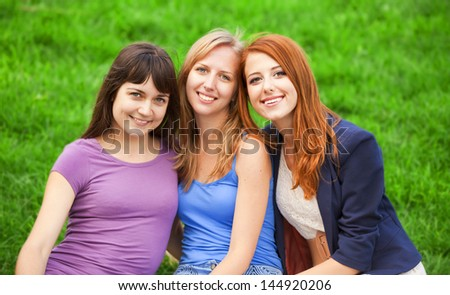 Redhead, brunette and blonde girl sitting at green grass in the park. - stock photo