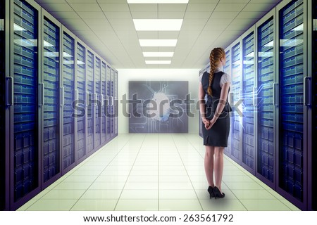 Redhead businesswoman with hands behind back against server room with towers