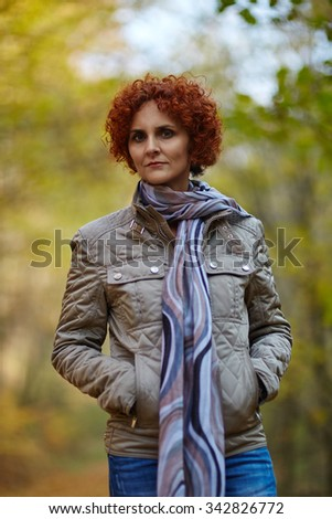 Redhead caucasian woman walking in the forest on an alley covered in fallen leaves - stock photo