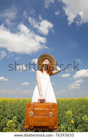 Redhead enchantress with suitcase at spring rapeseed field. - stock photo