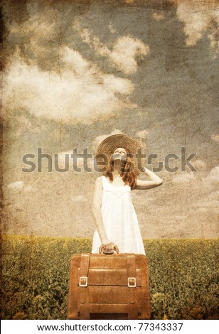 Redhead enchantress with suitcase at spring rapeseed field. Photo in old image style. - stock photo