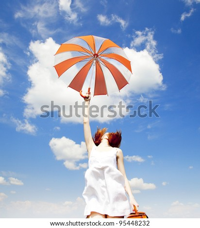 Redhead enchantress with umbrella and suitcase at spring