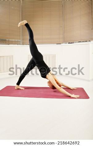 Redhead exercising downward facing dog yoga pose leg raised - stock photo