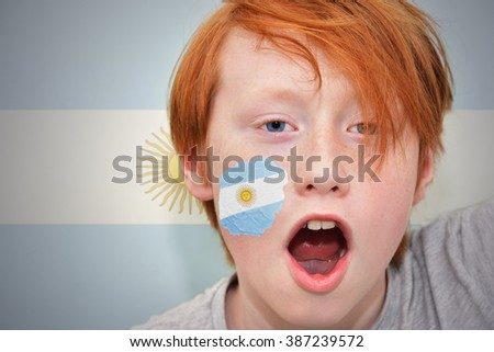 redhead fan boy with argentinean flag painted on his face. on the  argentinean flag background - stock photo