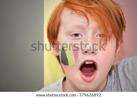 redhead fan boy with belgian flag painted on his face. on the belgian flag background - stock photo