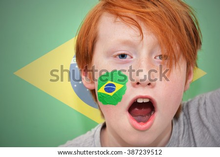 redhead fan boy with brazilian flag painted on his face. on the brazilian  flag background - stock photo