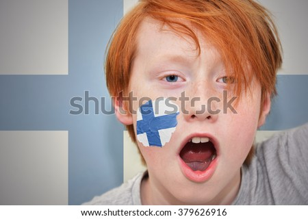 redhead fan boy with finnish flag painted on his face. on the finnish flag background - stock photo