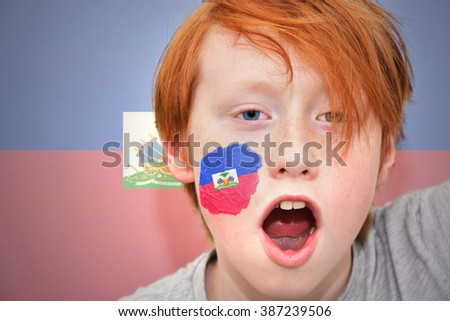 redhead fan boy with haitian flag painted on his face.  - stock photo