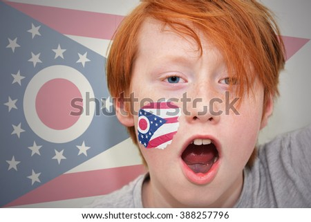 redhead fan boy with ohio state flag painted on his face.  - stock photo