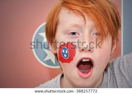 redhead fan boy with tennessee state flag painted on his face.  - stock photo