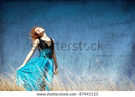 Redhead girl at windy field. - stock photo