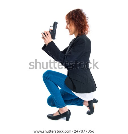 Redhead girl holding a pistol  - stock photo