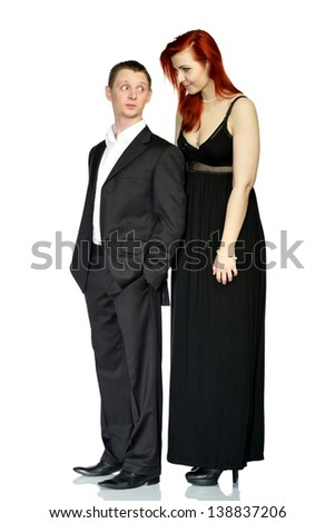 Redhead girl in a black dress and a man in a suit posing in the studio. Isolated on a white background - stock photo