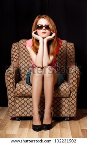Redhead girl in armchair. 70s