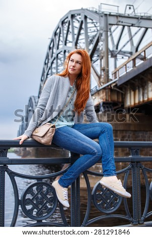 Redhead girl in casual clothes posing on paraphet near the river - stock photo