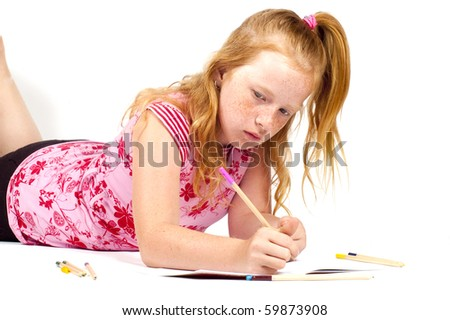 redhead girl is doing her homework isolated on white