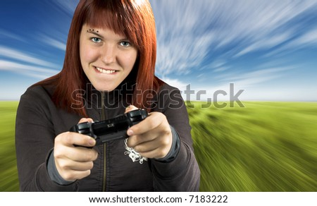 Redhead girl joyfully playing video games console. Background is conceptualized to be used for a driving game (motion blur). Shot in studio, processed in PS with a composite background. - stock photo