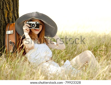 Redhead girl sitting near tree with vintage camera. - stock photo