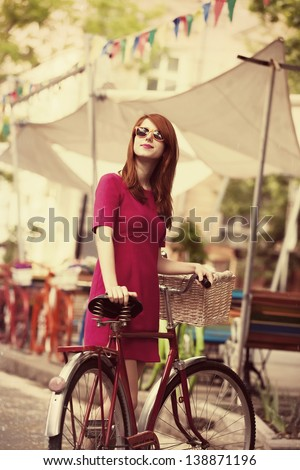 Redhead girl with bike at outdoor, city. - stock photo